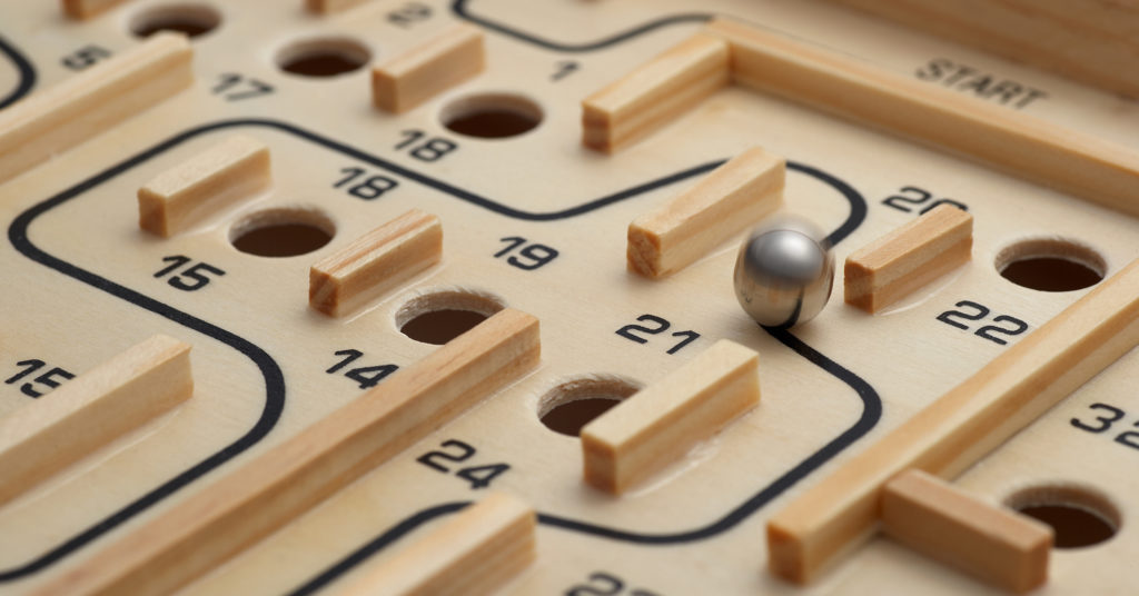 A challenging wooden maze game where a ball is manouvered to miss the holes.